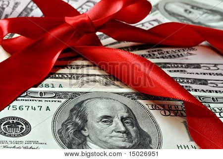 Holiday gift of money.  100 and 50 dollar bills with red satin ribbon.  Macro with shallow dof.