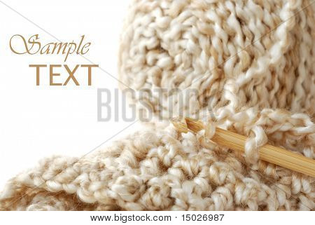 Silky textured yarn with bamboo crochet hook and detail of completed stitches.  Macro with shallow dof and copy space.