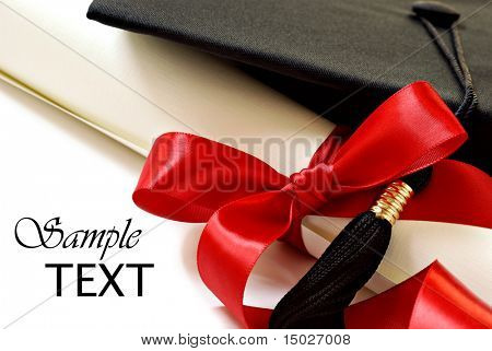 Diploma with red ribbon and black graduation cap on white background with copy space.  Macro with shallow dof.