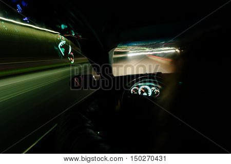 Driving at night. View from inside the car. Photo with a long exposure. Taken with a wide-angle optics.