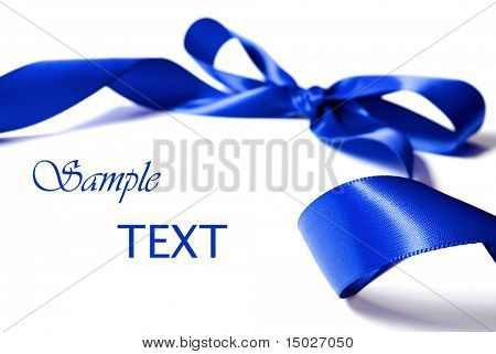 Shiny blue satin ribbon on white background with copy space. Macro with extremely shallow dof.