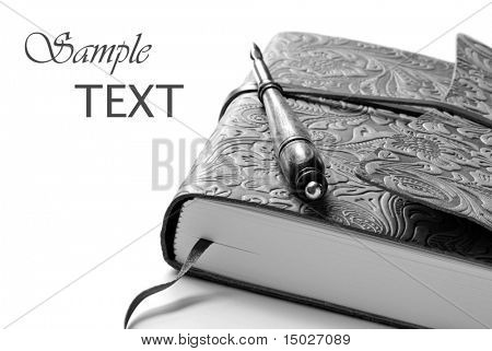 Elegant leather journal with calligraphy pen. Black and white macro with shallow dof and copy space.