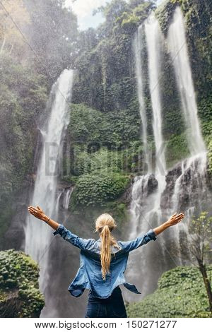 Excited Woman Standing By Waterfall