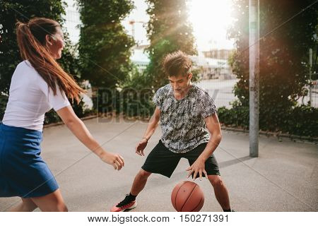 Two young man and woman on basketball court dribbling with ball. Friends playing basketball on court and having fun.