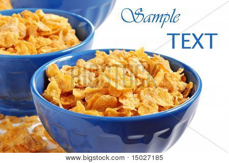 Corn flakes in blue ceramic bowls on white background with copy space.  Macro with shallow dof.