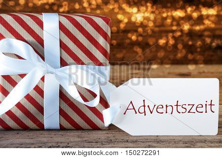 Macro Of Christmas Gift Or Present On Atmospheric Wooden Background. Card For Seasons Greetings, Best Wishes Or Congratulations. White Ribbon With Bow. German Text Adventszeit Means Advent Season