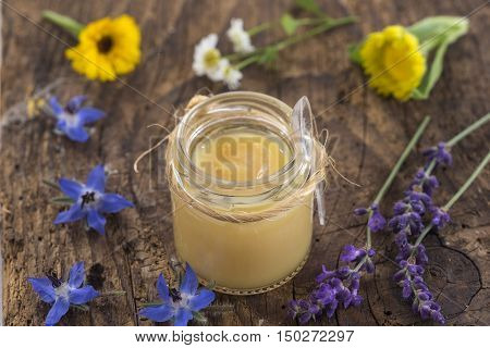 raw organic royal jelly in a small bottle on s wooden board