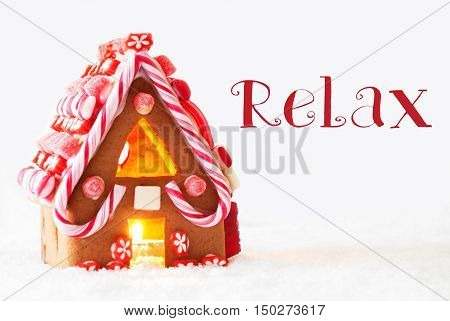 Gingerbread House In Snowy Scenery As Christmas Decoration With White Background. Candlelight For Romantic Atmosphere. English Text Relax