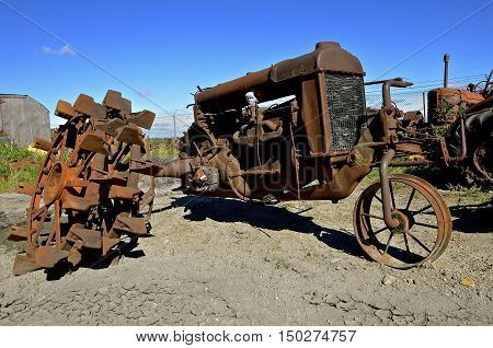 A very old one wheeled rusty tractor have several rear lugged wheels.