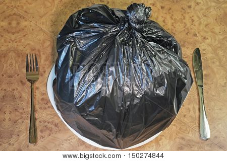Food garbage and poor nutrition concept as a table setting with a black plastic garbage bag on a dinner plate with a knife and fork as a metaphor for a bad diet or doggy bag symbol.