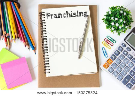 franchising text message on white paper and office supplies, pen, paper note, on white desk , copy space / business concept / view from above, top view