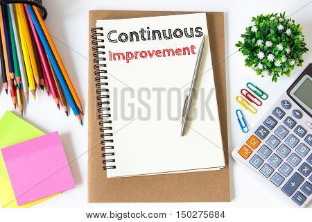 continuous improvement text message on white paper and office supplies, pen, paper note, on white desk , copy space / business concept / view from above, top view