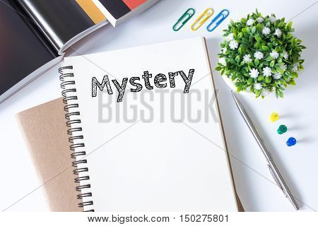 Mystery word message on white paper book and copy space on white desk / business concept / top view