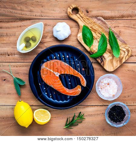 Raw Salmon Fillet In The Black Plate With Ingredients Olive Oil ,himalayan Salt, And Herbs Sweet Bas