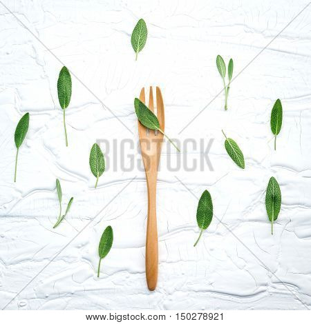 Closeup  Fresh Sage Leaves  With Fork On White Wooden Background . Alternative Medicine Fresh Salvia