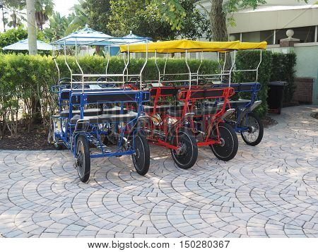 several pedal surreys sit unused at a vacation resort