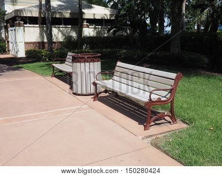 two garden benches and a garbage can by a sidewalk