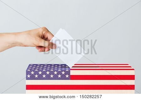 voting, civil rights and people concept - male hand putting his vote into ballot box on usa presidential election day