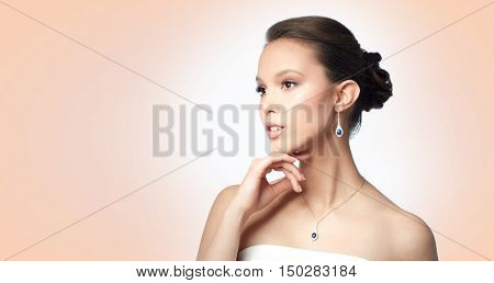 beauty, jewelry, wedding accessories, people and luxury concept - beautiful asian woman or bride with earring and pendant over beige background