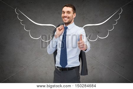 business, angel investor, safety, security and people concept - smiling young businessman with wings drawing showing thumbs up over gray concrete background