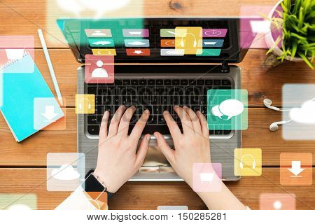 multimedia, people and technology concept - close up of woman or student typing on laptop computer with menu icons on screen, notebook and earphones on wooden table