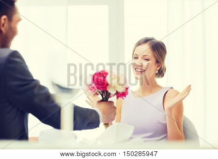 restaurant, couple and holiday concept - amazed woman recieving bouquet of flowers from husband or boyfriend at restaurant