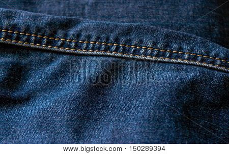 Detail of blue jeans with stitched seam. Close-up.