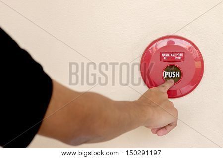 closeup shot of human hand pushing fire alarm. The hand of man is pushing fire alarm switch on the wall.