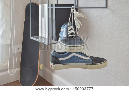 pair of casual blue sneaker shoes hanging on book shelve at home