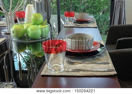 table set on wooden dining table in modern style dining room interior