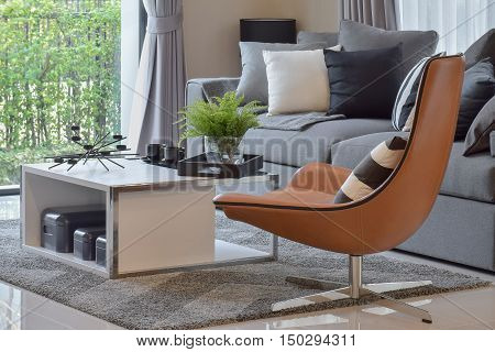 living room with plant in vase and black pattern pillows on modern leather chair