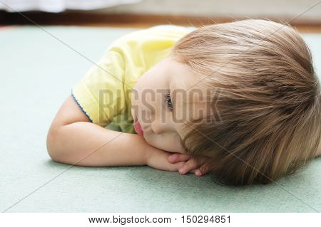 sulky little girl lying on the cover indoor