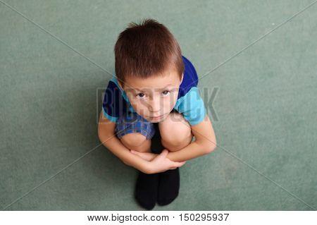Little boy looking up sitting folding knee