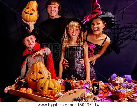 Children on Halloween party making carved pumpkin. Knock knock, trick or treat. Who are you.