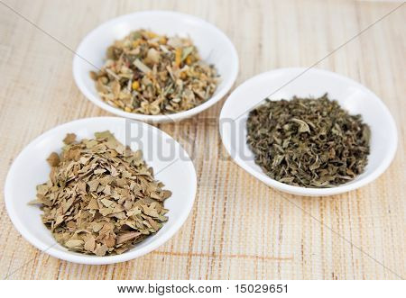 Herbal Teas In Small White Bowls On Natual Matting