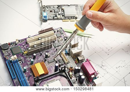 Man using soldering tool for motherboard repair, close up