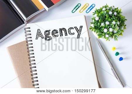 Agency message text on white paper book on white desk / business concept / top view