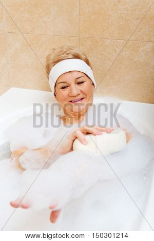 Bathing woman relaxing with sponge