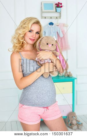 the happy pregnant woman holds a plush toy