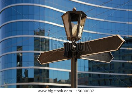 Blank signpost with ancient lamp against business building