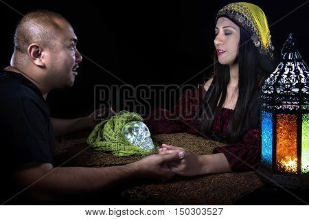 Psychic or fortune teller gypsy with a client doing a seance telepathic ritual