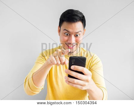 Asian man is playing mobile game in his smartphone.