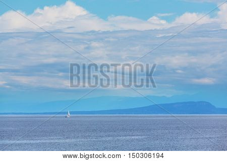 Beautiful seascape along Pacific coast of British Columbia, Canada, with rocky shoreline. Blue sky in sunny weather.