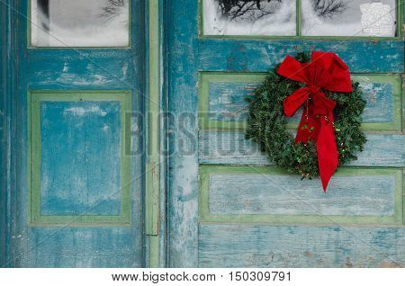 Wreath hanging on historic buliding front door at christmas