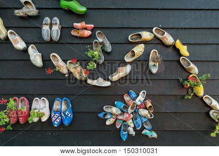 An image of clogs in a wall as flowerpots. Traditional Dutch wooden clogs hanging at wooden wall Souvenir from Holland.