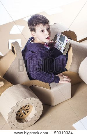 photo of young racer on a cardboard racing car.