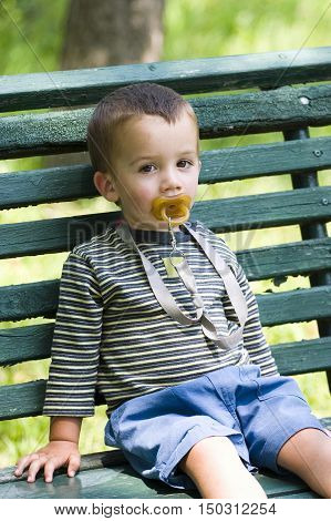 Boy with pacifier sat on bench outdoors