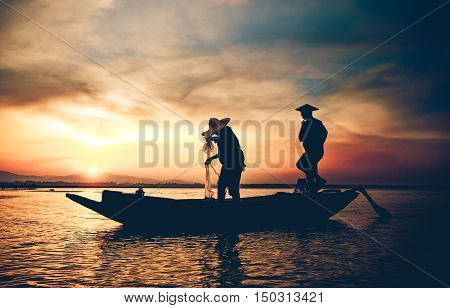Silhouette of traditional fishermen throwing net fishing lake at sunrise timethailand (The casting people living along the River)