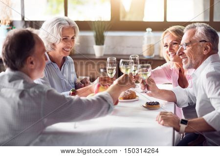 For our family. Friendly big lovely family raising their glasses and having celebration meal while sitting in a cozy kitchen.