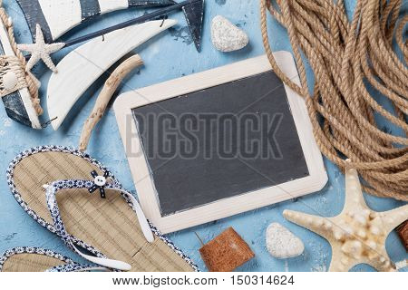 Beach accessories. Flip-flops, boat, seashells and blackboard for your text on stone background. Top view with copy space